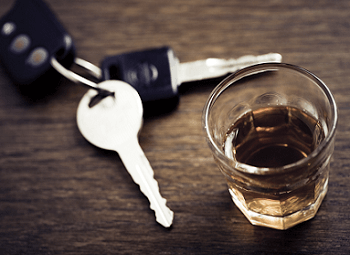 set of car keys on a dark wood table next to a glass of alcohol