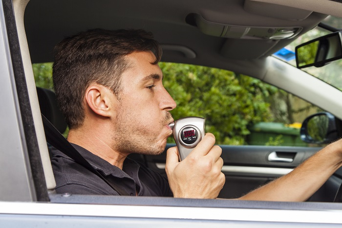 Man Blowing Into Ignition Interlock Device