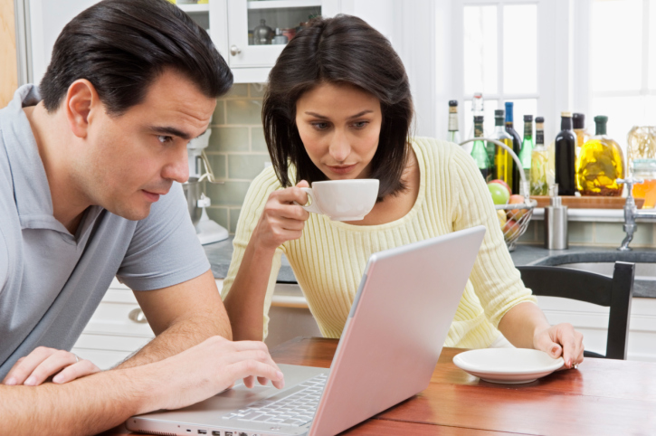 Couple Shopping Online at Kitchen Table